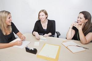 Das Bild zeigt drei Frauen im Büro - Motto: Produtivität setzt perfektes Teamwork voraus!